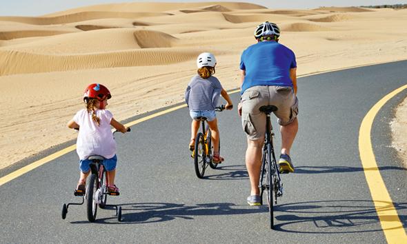 פארק מושרף בדובאי. משפחות רוכבות על אופניים