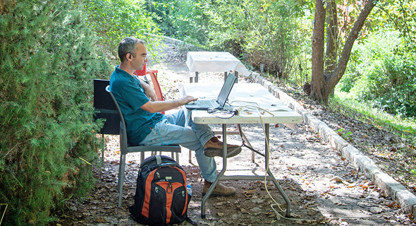 A man works outside on his computer at the Jerusalem Botanical Gardens. Photo: Yoav Dudkevitch