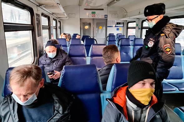 שוטר במוסקבה בודק עטיית מסיכות באוטובוס, צילום: איי פי