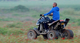 צעיר נוהג ב טרקטורון בתוך שדה כלניות פנאי, צילום: רועי עידן