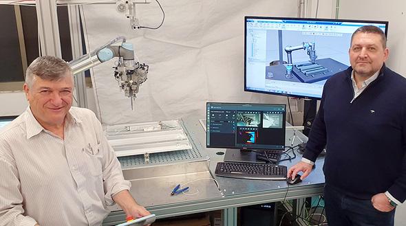 """משמאל: עומר עינב, מנכ""""ל חברת פוליגון, מפתחת מערכת ההרכבה הרובוטית, מימין: אלכס גרינברג, מנהל בקבוצת הסימולציה בסימנס תוכנה לתעשייה בישראל, עם התאום הדיגיטלי של מערכת ההרכבה"""