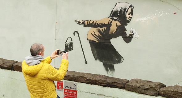 ילדה מתעטשת. ציור קיר של הצייר אמן בנקסי , צילום: איי אף פי