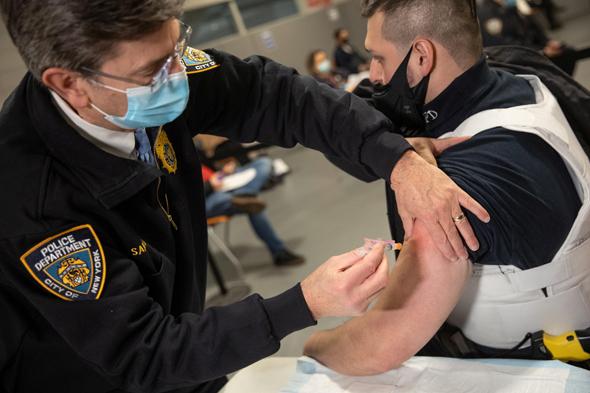 שוטר בניו יורק מקבל חיסון, צילום: רויטרס