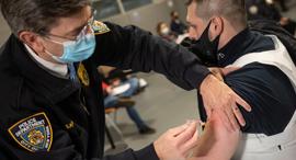 שוטר מתחסן נגד קורונה בקווינס, ניו יורק, צילום: רויטרס