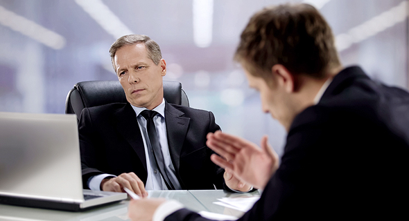 A manager looking at figures while ignoring his employee. Photo: Shutterstock