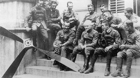 מנפרד יושב עם אנשיו, ראשו חבוש. לצידם מדחף של מטוס שהפילו