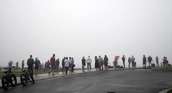 צופים מסתכלים על ניסיון הנחיתה של המעבורת של SpaceX בערפל כבד, צילום: רויטרס