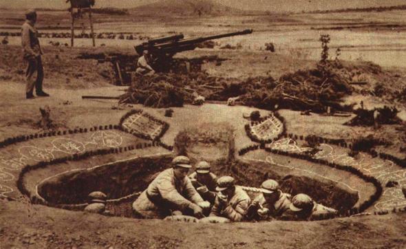"""שוחת פיקוד בסוללת נ""""מ סינית, מאחוריה תותח 100 מ""""מ, צילום: Wikimedia"""