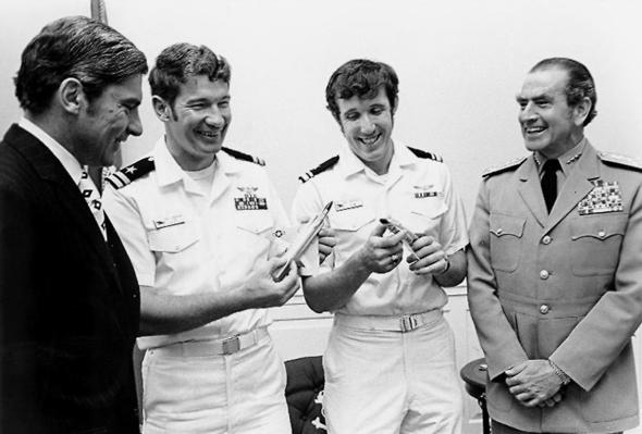 מימין: אדמירל אלמו זומוולט, הגיבורים דריסקול וקמינגהאם, ושר הימייה ג'ון וולטר בביקור במשרדו בוושינגטון