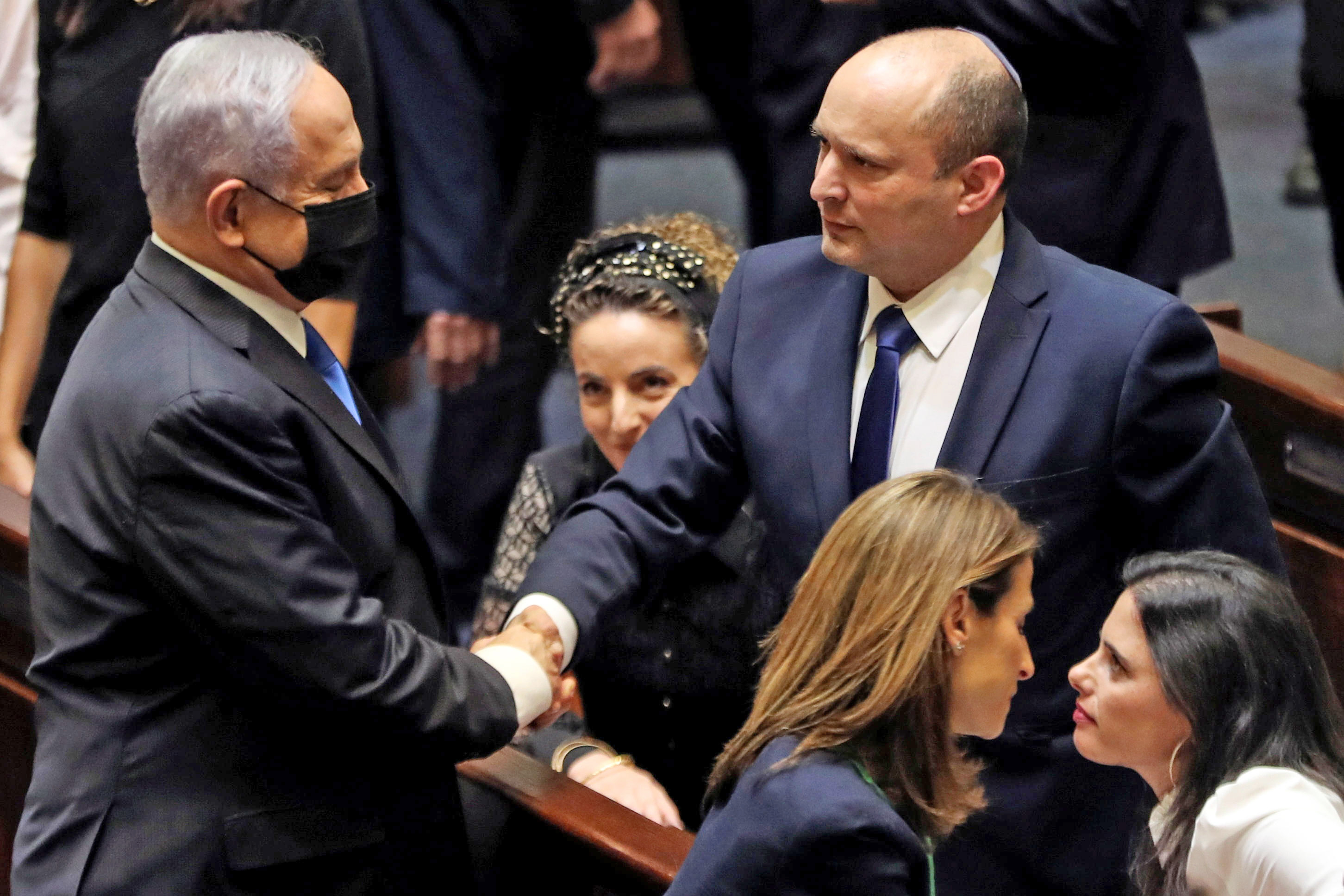 Incoming Prime Minister Naftali Bennett (right) shakes hands with Benjamin Netanyahu. Photo: Reuters