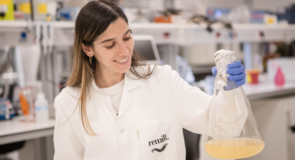 Lab technician Maya Danino holds up Remilk