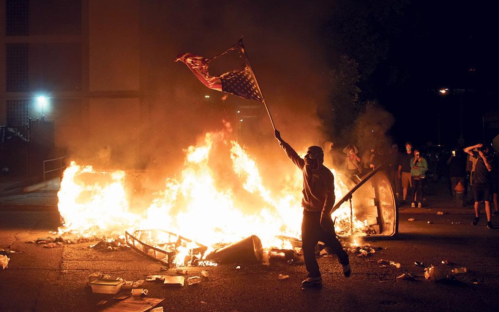 מוסף שבועי 2.7.20 מפגין בסנט לואיס שורף את הדגל האמריקאי במחאה על מותו האלים של ג'ורג' פלויד