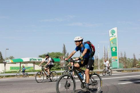 רוכבי אופניים על רקע תחנת דלק דור אלון , צילום: פטריסיה בן עזרא