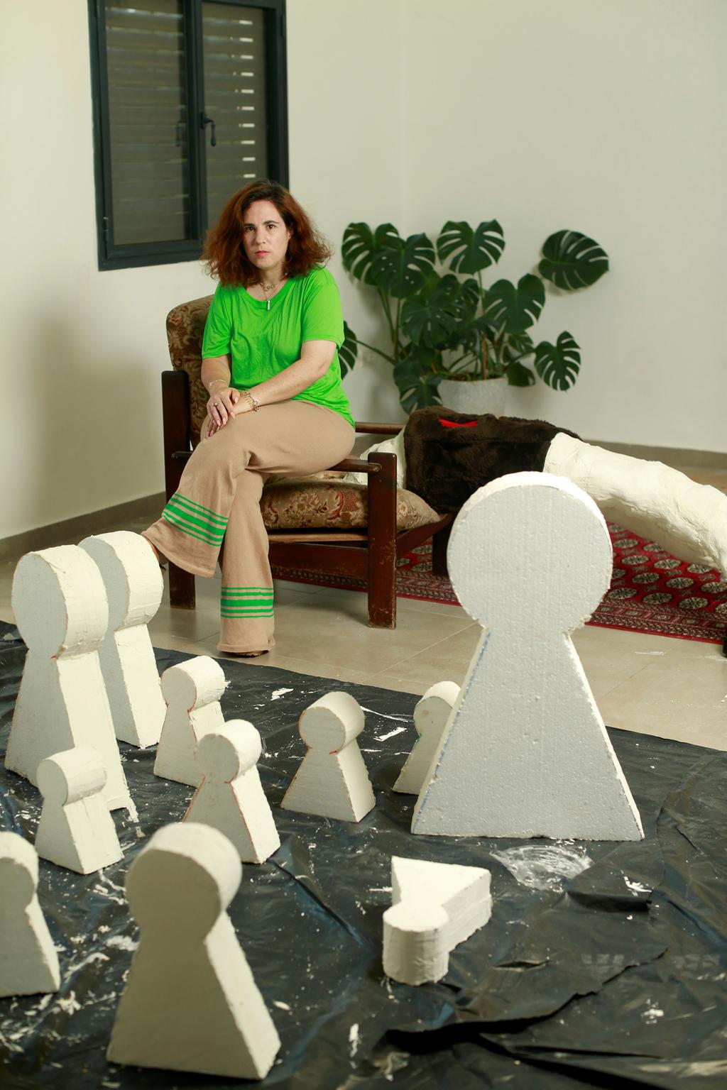 מיטל אבירם בביתה על רקע עבודות של עידית גלעד פנאי