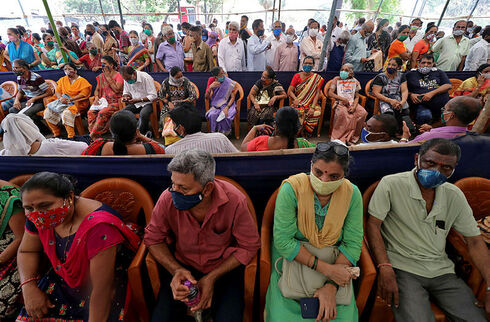 אנשים מחכים בתור לקבלת חיסון לקורונה במומבאי, רויטרס