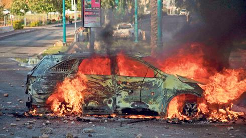 """רכב עולה באש בעימותים בלוד, בשבוע שעבר. """"להשפיע על קצב ריפוי החברה"""", צילום: איי אף פי"""