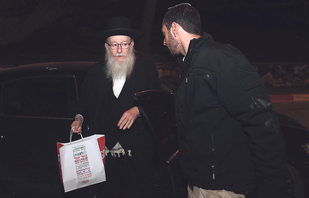 יעקב ליצמן עם שקית המעדנייה שעליה ניסה להגן בניגוד לחוק
