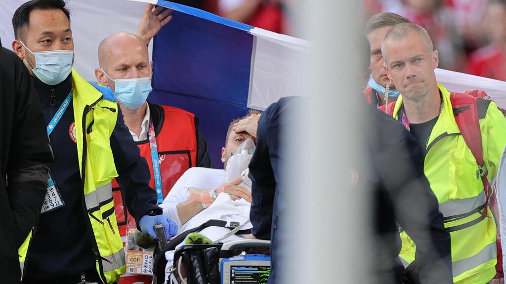 כריסטיאן אריקסן שחקן דנמרק מפונה מהמגרש לאחר שהתמוטט ועבר החייאה