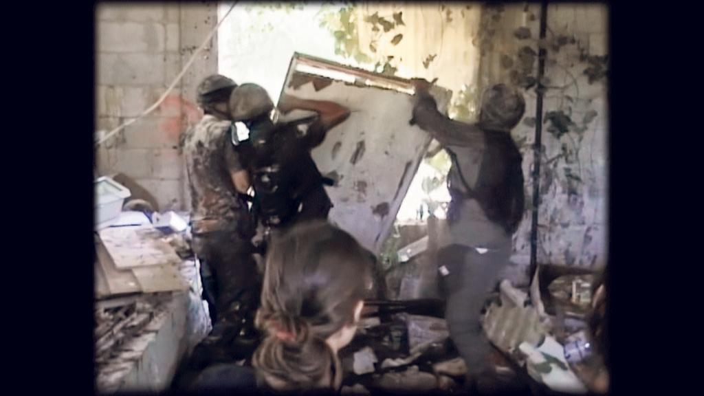 פנאי יהודית כהנא בגבה למצלמה מול חיילים מתוך הסרט