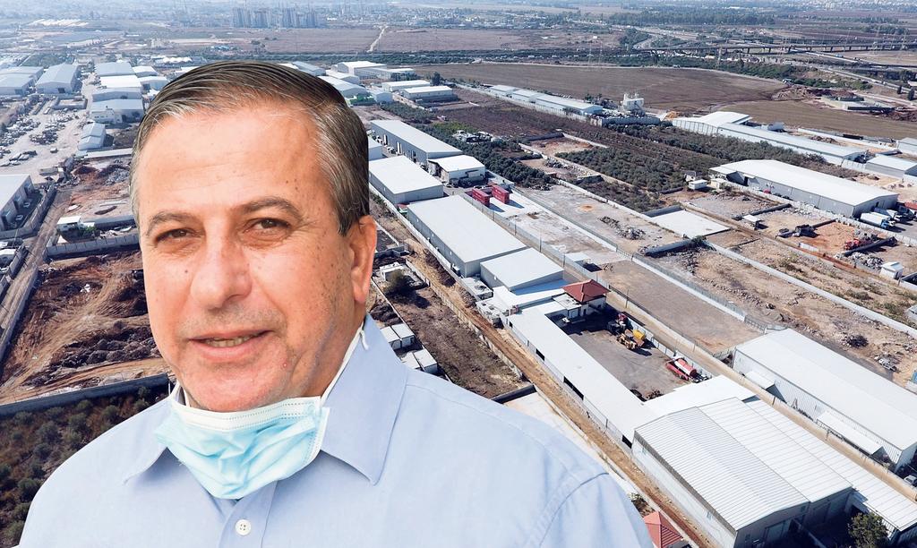 ראש העירייה עאדל בדיר ברקע אזור התעשייה של כפר קאסם