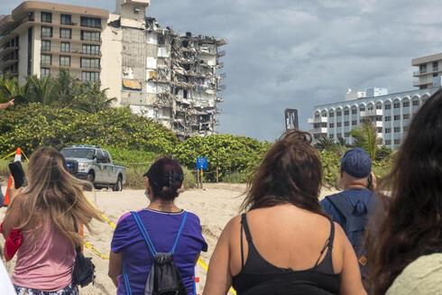 עוברי אורח מביטים בהריסות המגדל, EPA