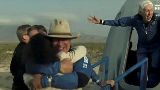 משמאל ג'ף בזוס מתחבק עם נחיתתו