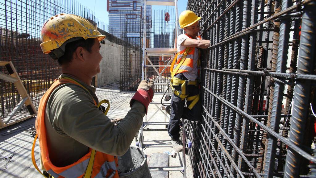 פועלים באתר בנייה. היקפי העובדים אינם תואמים את צורכי הענף, צילום: שאול גולן