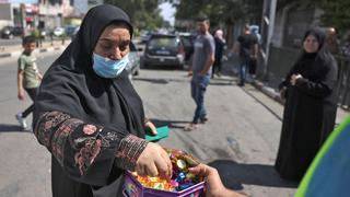 אשה מקבלת ממתקים שמחולקים ברחוב ב רצועת עזה, צילום: AFP