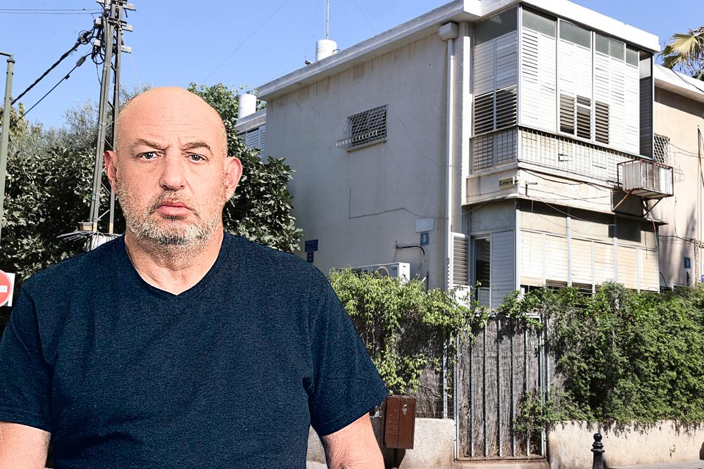 הראל ויזל על רקע אחד הבניינים שייהרסו בשכונת נחלת יצחק תל אביב ובמקומם יבנה מגדל של 27 קומות